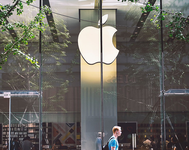 Man walking past Apple Store Window with Brand Mark in background