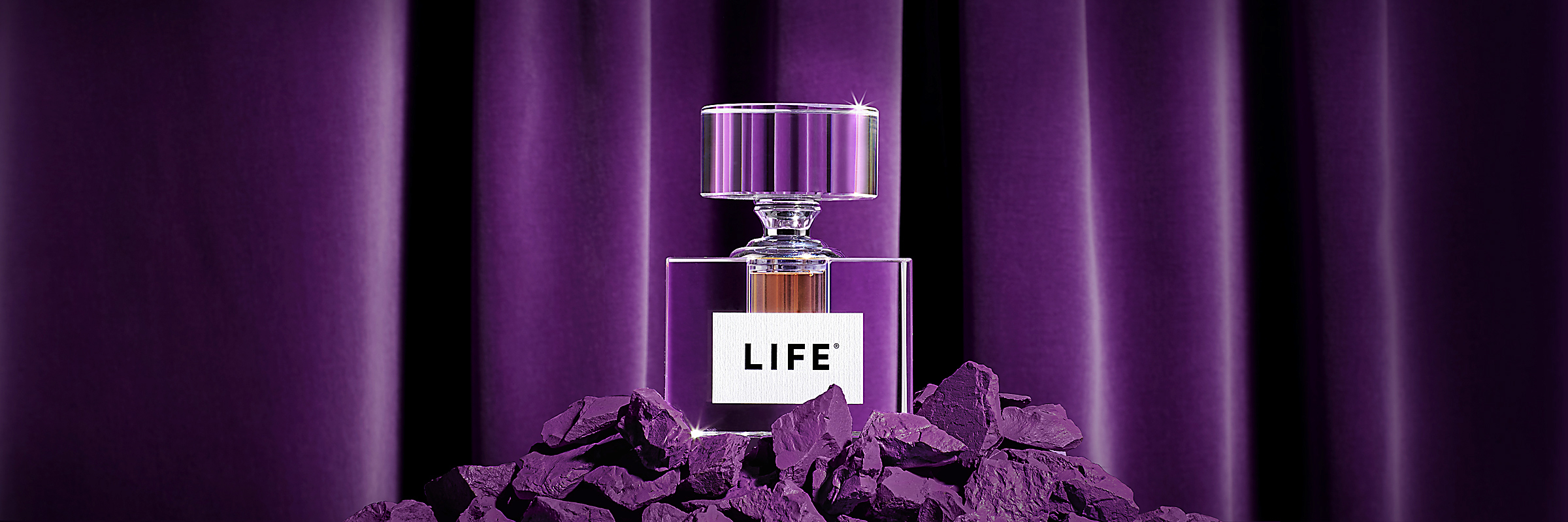 Bottle of Life on purple rocks in front of a purple curtain