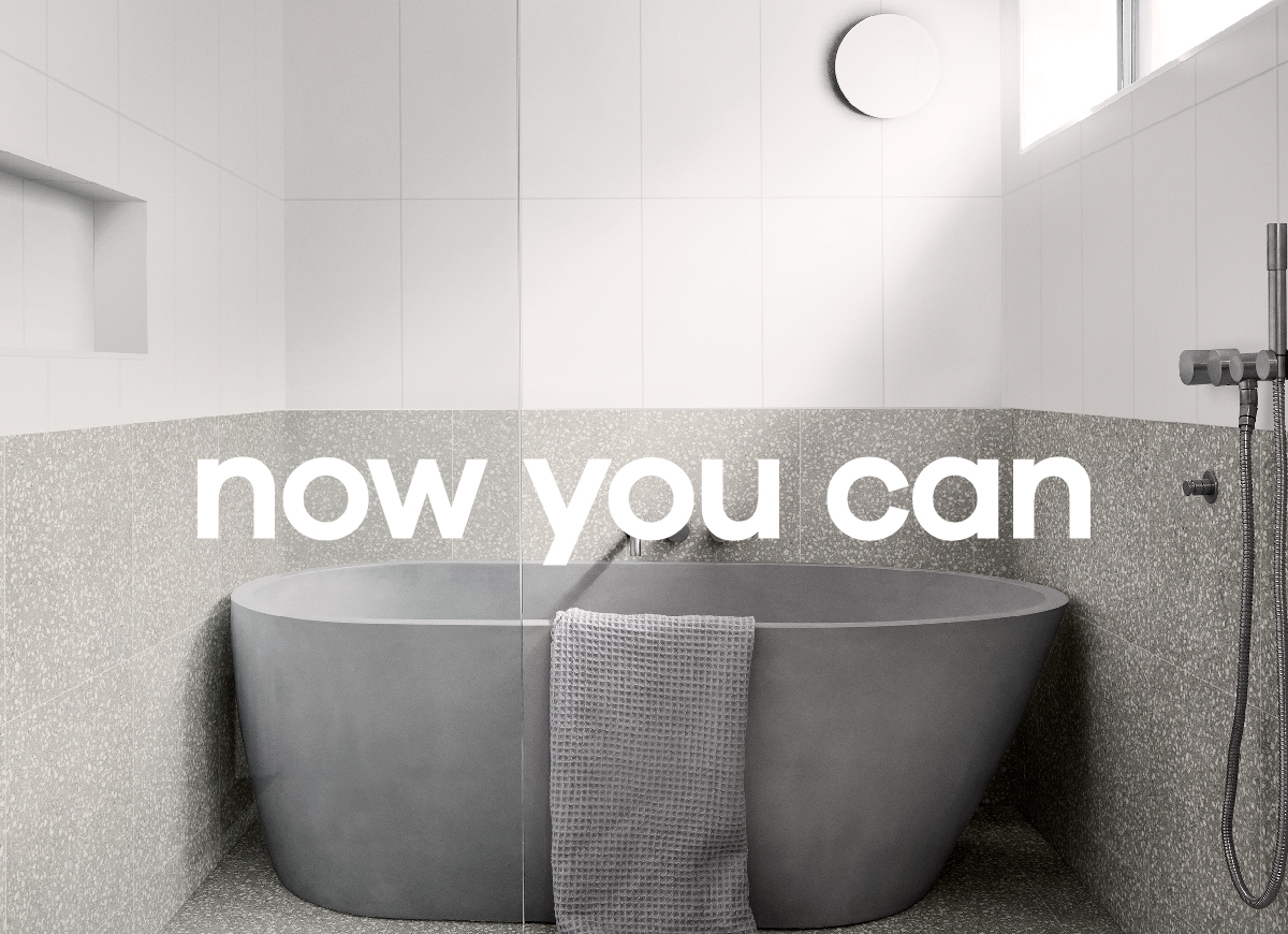 Grey Stone Bath in white tiled bathroom with Now You Can text for National Tiles advertising campaign