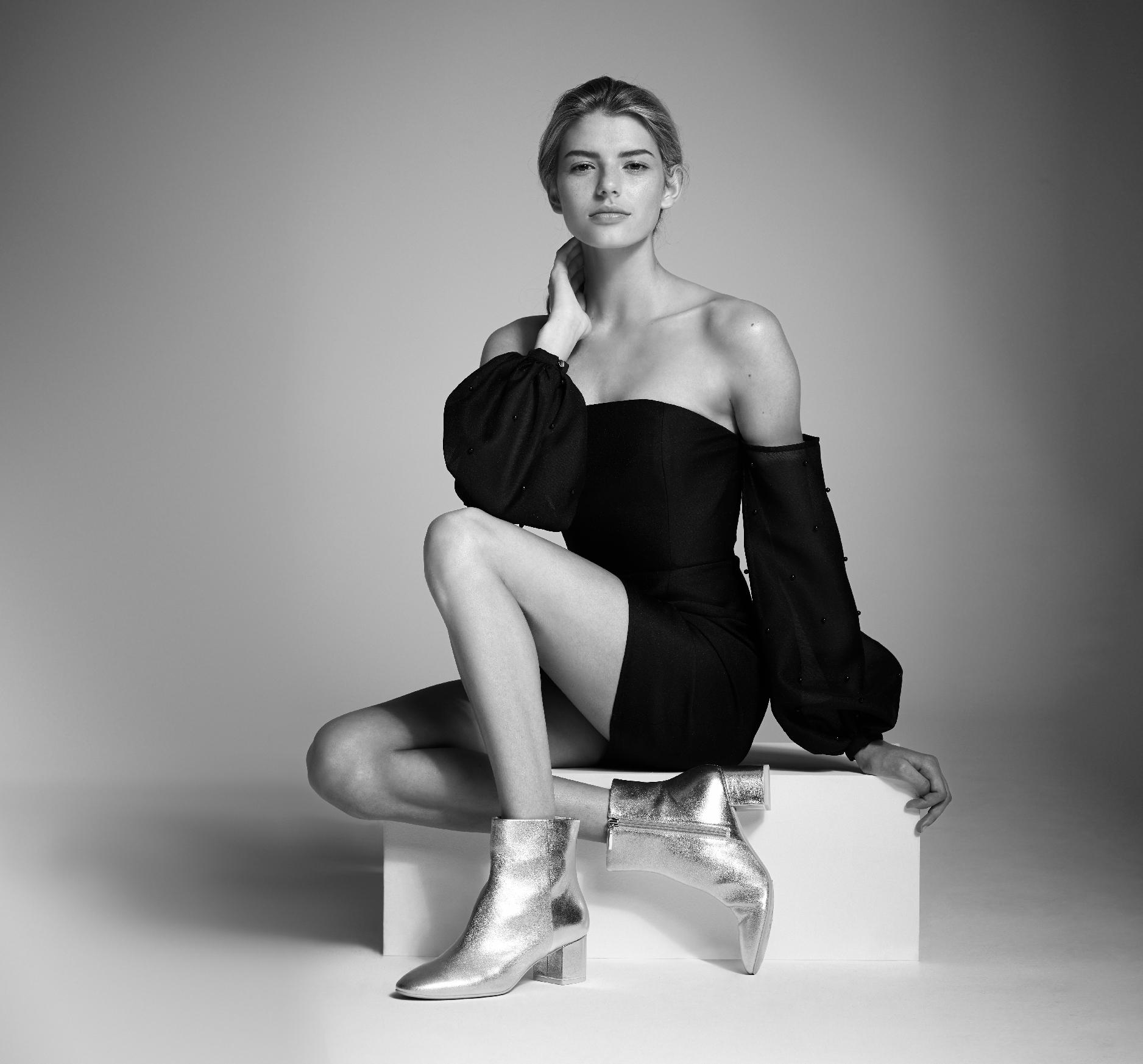 Wittner Brand Advertising still of model girl sitting on a white block wearing silver boots