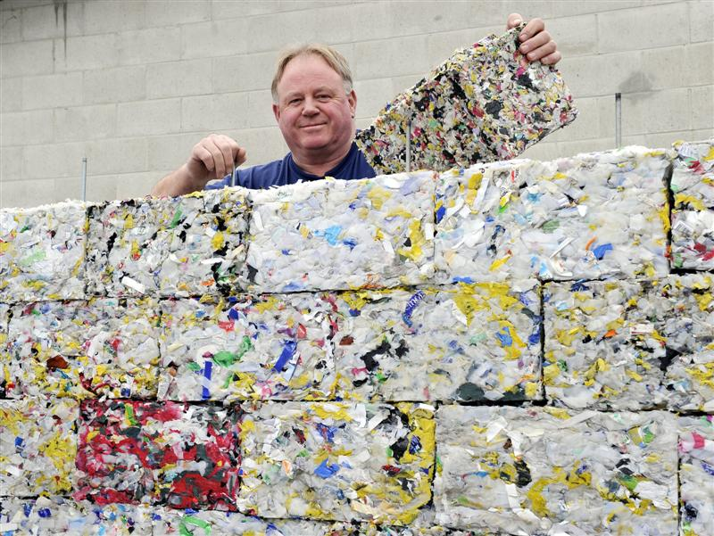 Dunedin Man Peter Lewis Shows Off Bricks of Recycling